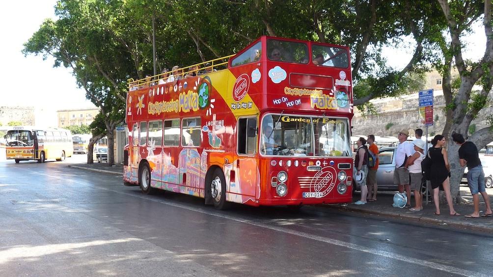 Guests board a double decker tour bus in Malta