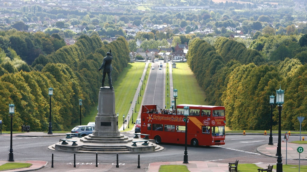 Show item 2 of 10. Hop on hop off double decker bus driving past a park in Belfast