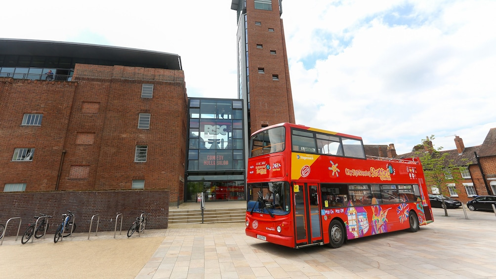 A hop on hop off bus driving past a modern building in Stratford upon avon