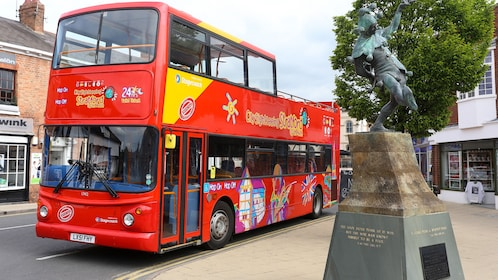 A hop on hop off bus driving past a statue in Stratford upon avon