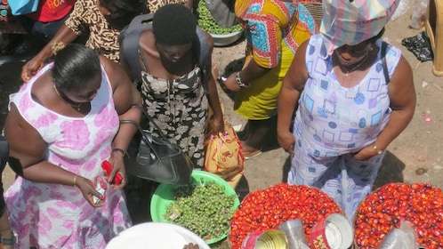 Women perusing goods on sale at an open-air market in Accra