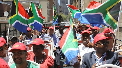 Tourists wave South African flags while on a bus tour
