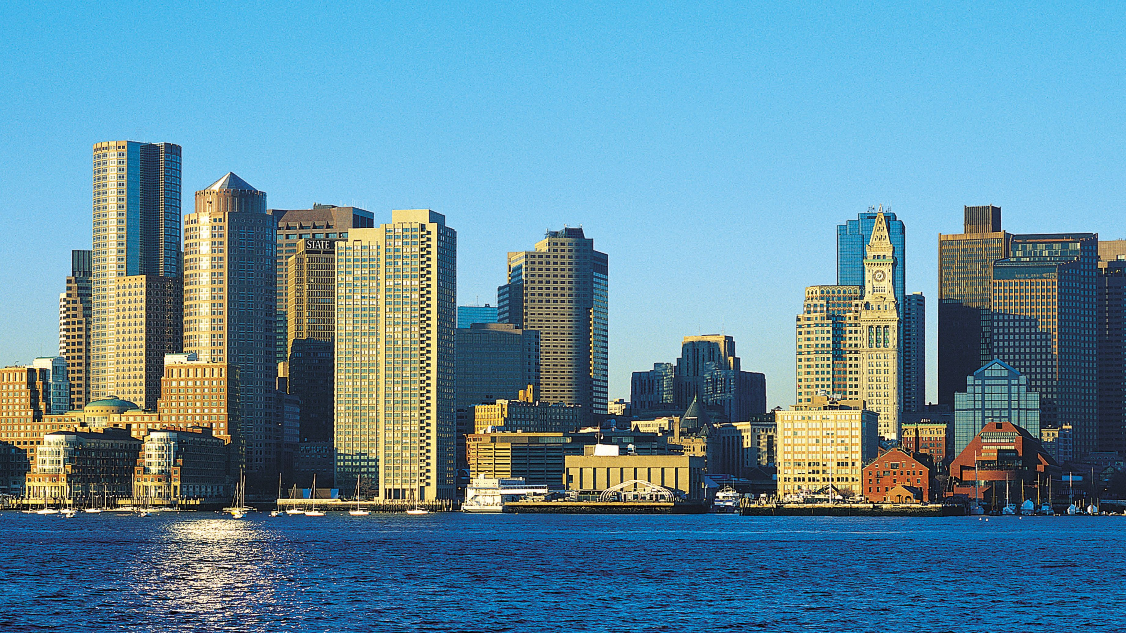 Sunlight hitting the tall buildings that line the coast of Boston Harbor