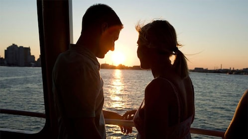 Silhouette of a couple at sunset on a boat in Boston Harbor