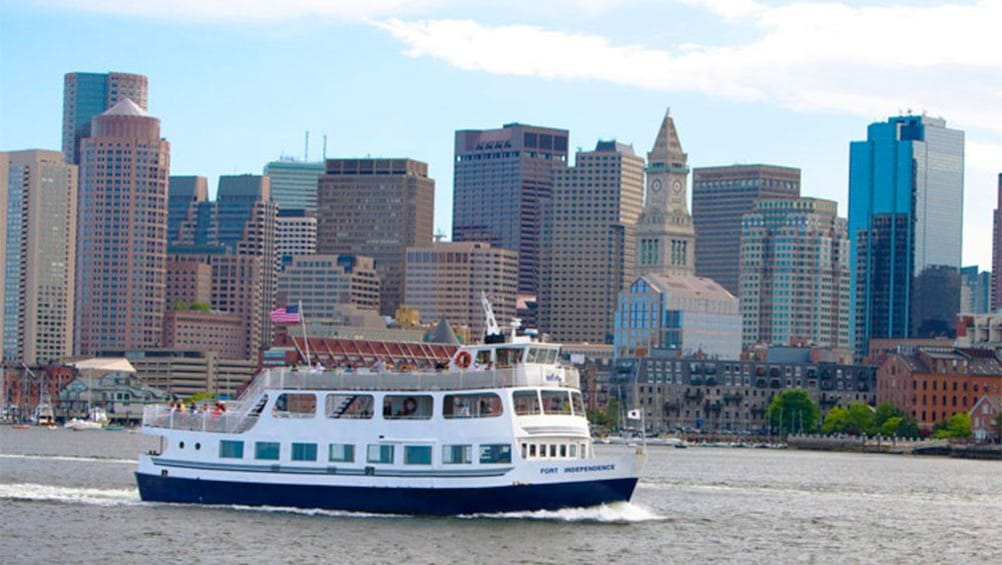 Show item 5 of 5. Boston Harbor Cruise boat with the skyscrapers of the city in the background in Boston