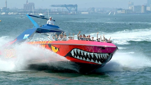 The Godzilla Thrill Boat with passengers speeding through the water in Boston Harbor