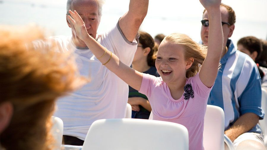 Young girl and family raising their arms as the Godzilla Thrill Boat zooms through the water in Boston Harbor