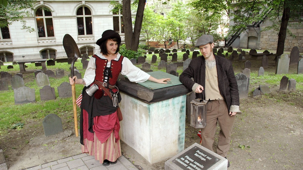 Show item 4 of 10. Ghosts and Gravestones Tour guides at a cemetery with a shovel in Boston