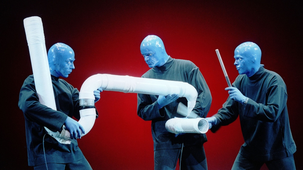 Show item 3 of 9. Blue Man Group drumming on a large pipe