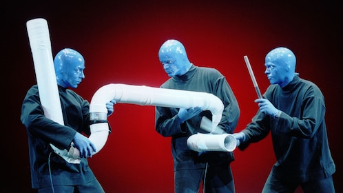 Blue Man Group drumming on a large pipe
