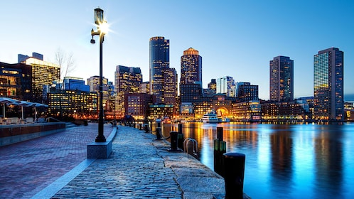 Waterfront walkway and the city at night in Boston