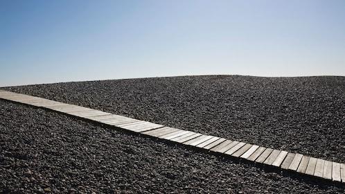 Long narrow boardwalk on a field of rocks in Massachusetts