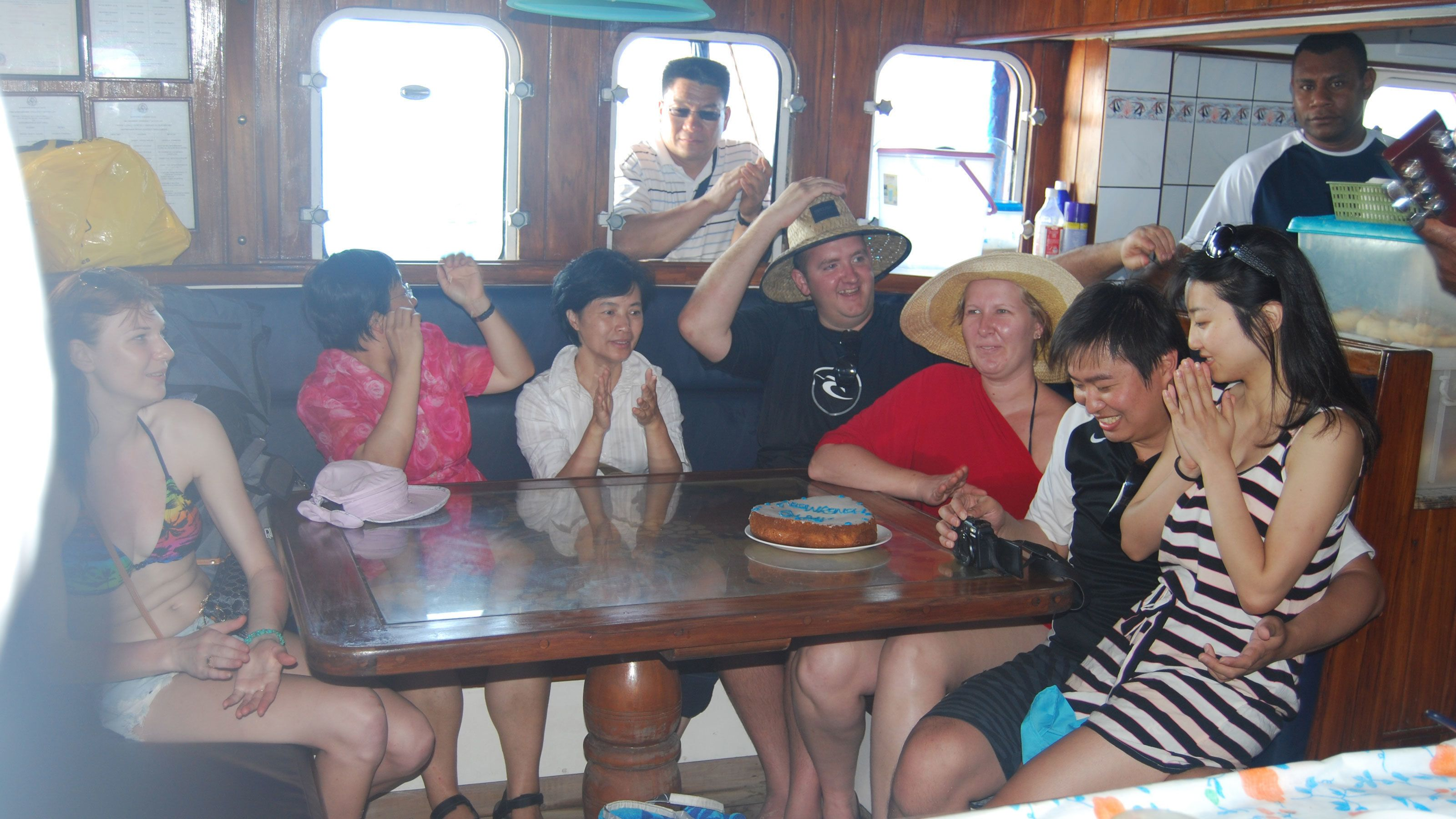 visitors celebrating with cake on the boat in Fiji