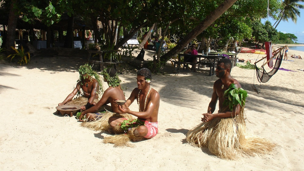 Show item 2 of 5. tribesmen resting at the beach at Robinson Crusoe Island in Fiji