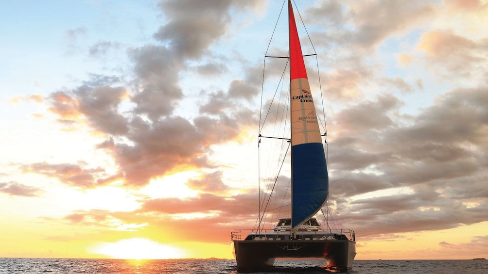 Show item 1 of 7. Catamaran sailing at sunset in Fiji
