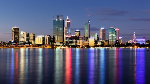 A view of the perth city skyline from a river at sunset