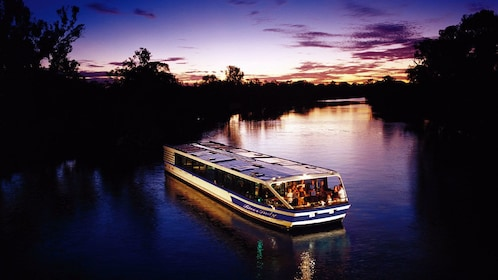A cruise boat sailing up a river in perth at sunset