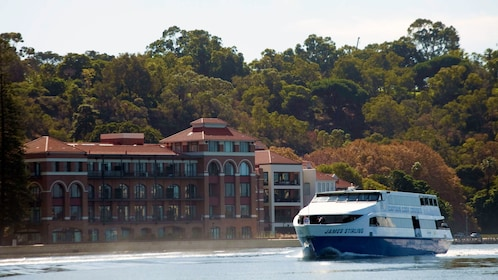 a cruise ship sailing past a mansion on the swan river