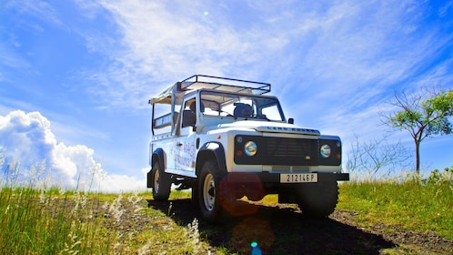 Close view of a 4x4 vehicle in Bora Bora parked on the grass with beautiful blue skies behind