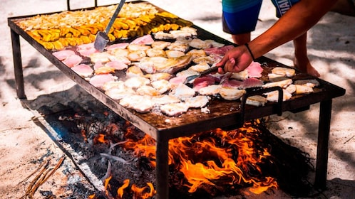 A fire heated grill cooking fish and chicken