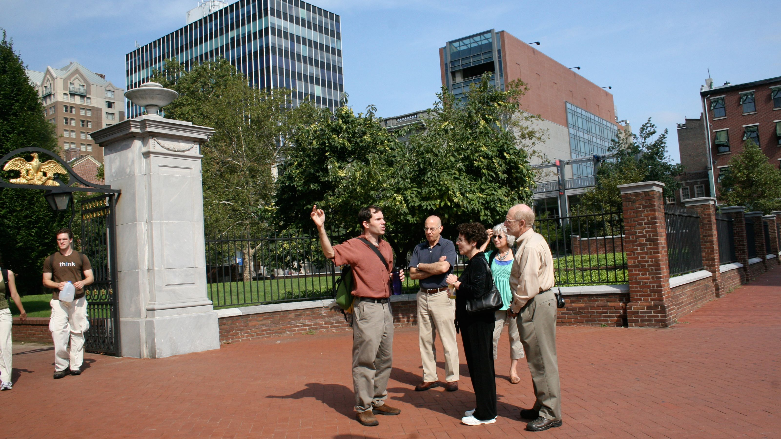 Tour guide with group in a red brick courtyard in Philadelphia