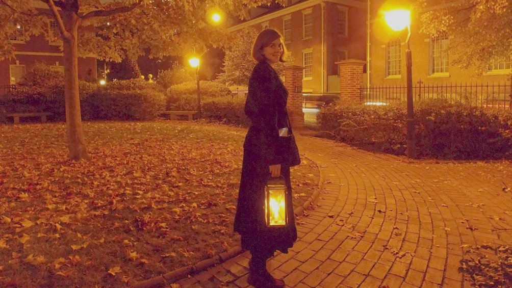 Show item 2 of 5. Woman carrying lantern in a courtyard at night in Philadelphia