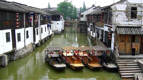 Four water boats parked along the water at the Zhujiajiao Water Village in Shanghai