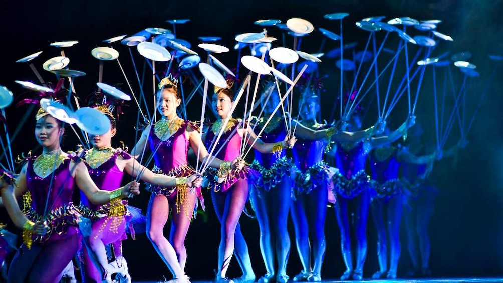 A row of female performers spinning china plates at the Award-winning Shanghai Acrobatics Show in Shanghai