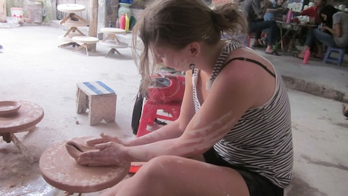Tourist making her own ceramics at the the floating village of Thanh Ha in Vietnam