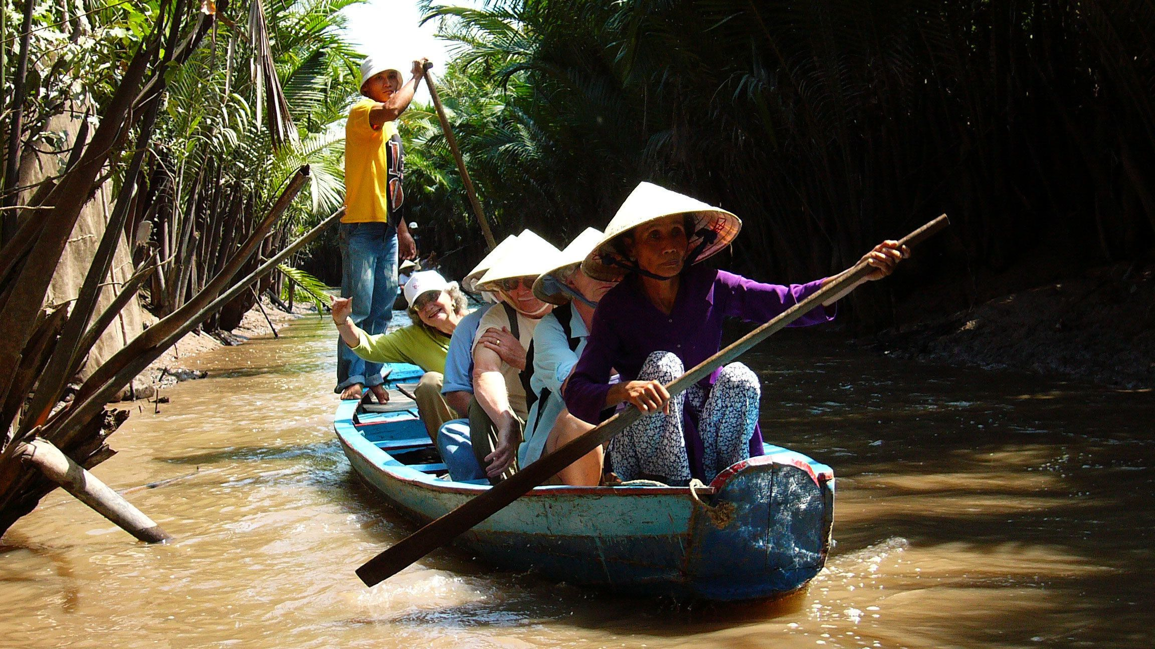 Tourists on a scenic river cruise along the beautiful Mekong River in Vietnam
