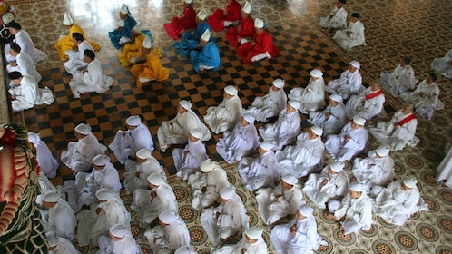View overhead inside the Private Tour to Cao Dai Temple overlooking the monks in Tay Ninh