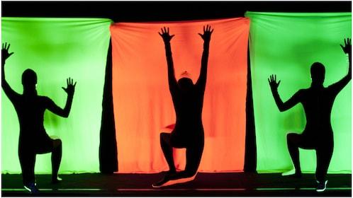Three black light dancers in green and orange backdrops
