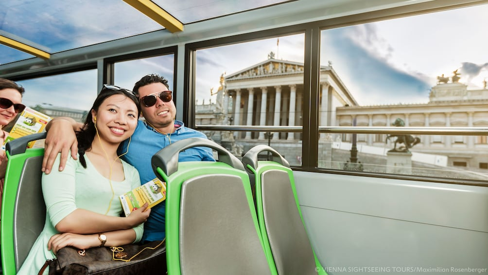 Couple listening to audio tour on Hop-On Hop-Off bus in Vienna
