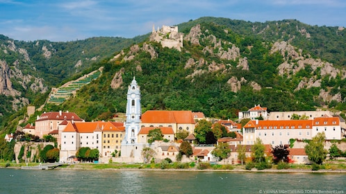 Bell tower stands above other buildings along river shore in Wachau