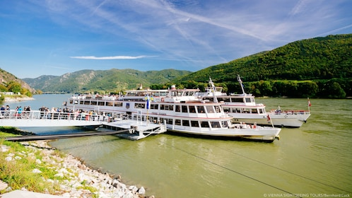Tour boats moored to pier on river in Wachau