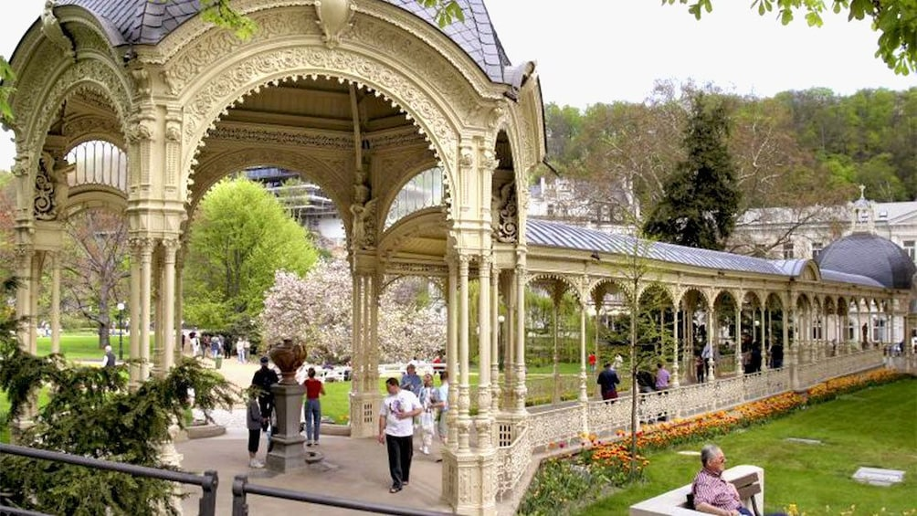 Show item 10 of 10. Tourists walking under a colonnade at a park in  Karlovy Vary