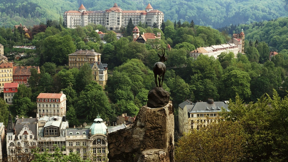 Show item 10 of 10. Leaping deer statue at a lookout with a view of the city in the distance in Karlovy Vary