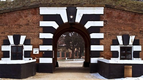 Black and white arches and brick wall at the entrance to a fortress at the Terezin Concentration Camp in Prague