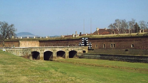 Bridge leading to black and white arched entrance to a fortress at the Terezin Concentration Camp in Prague