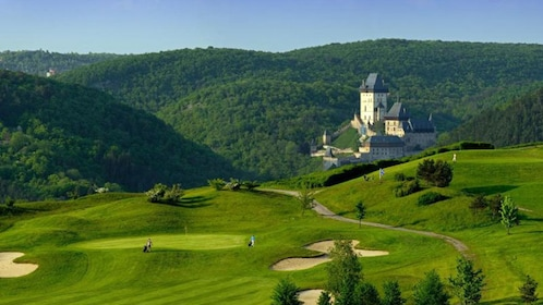 Sprawling green golf course with Karlstejn Castle in the distance in the Czech Republic