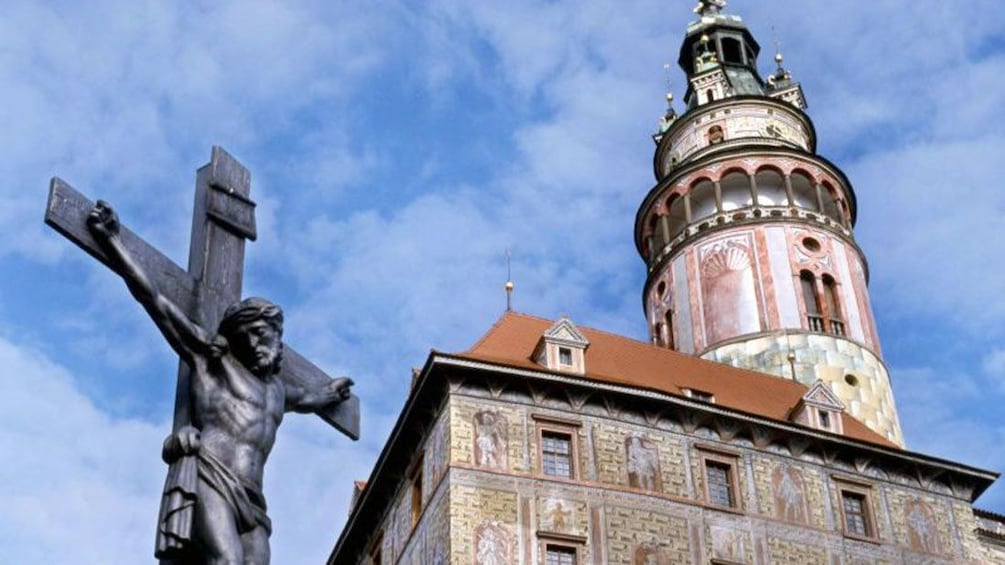 Show item 10 of 10. Statue of Christ on the cross and a bell tower in the background in Cesky Krumlov