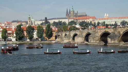Various tour boats on the Vltava Rive near the Charles Bridge in Prague