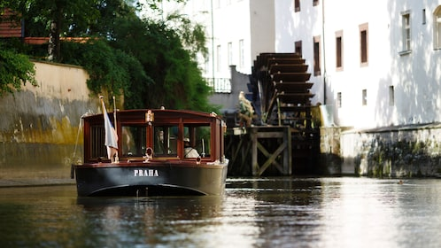 Tour boat on a canal near a water mill in Prague