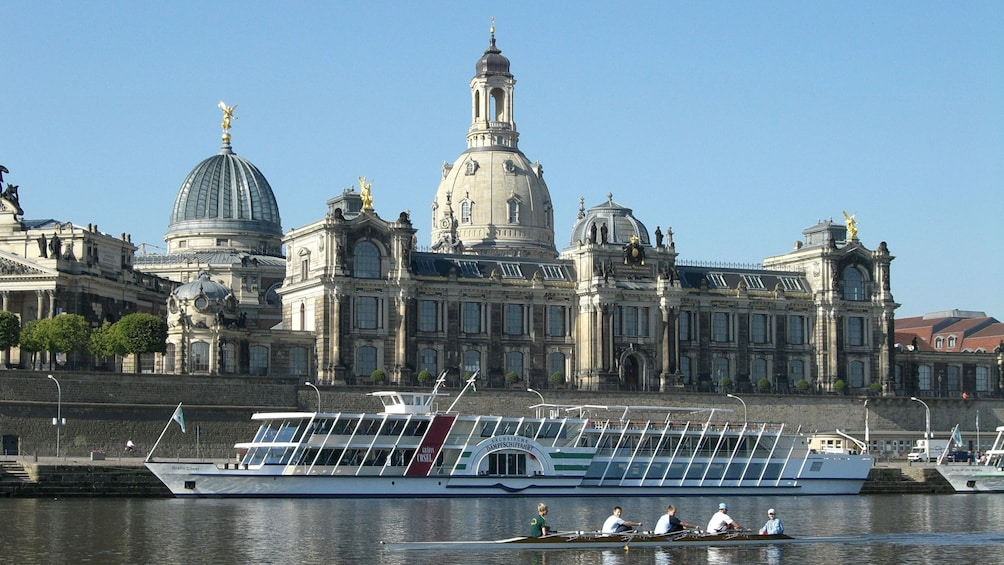 Show item 2 of 10. Boats line the bank the river near a cathedral in Dresden