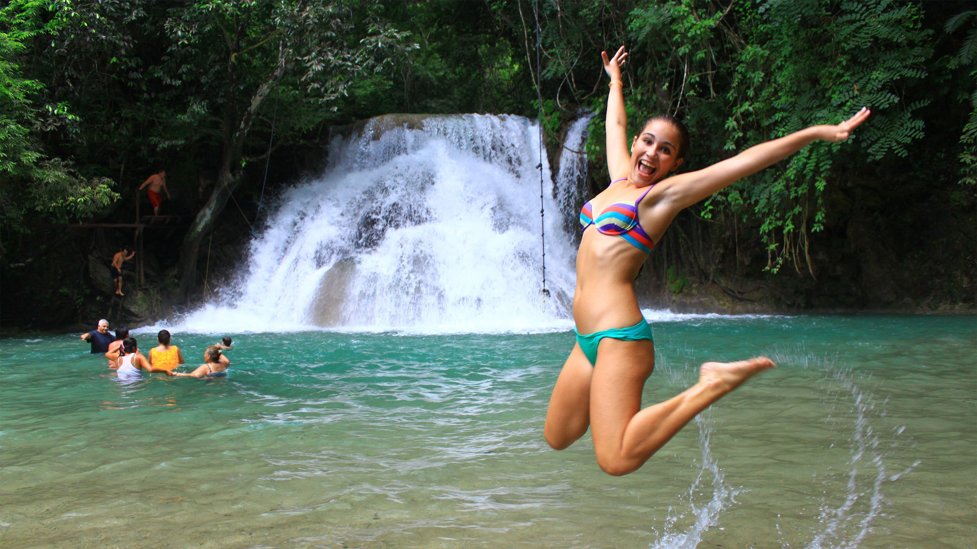 Woman jumping out of a lagoon at the Magic Waterfalls in Huatulco