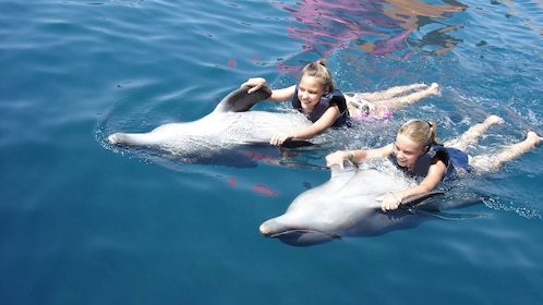 Two girls pulled along the water by dolphins in Ixtapa