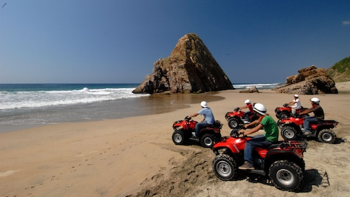ATV riding group on the sand along the water in Manzanillo