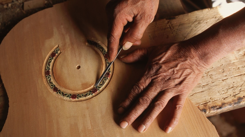 Man carving details into an acoustic guitar