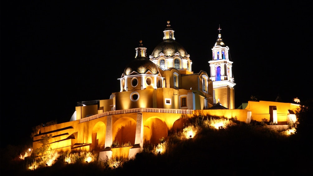 Cargar foto 1 de 5. Church lit up at night on top of the Great Pyramid of Cholula