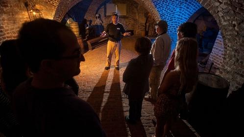 Tour group in an underground cellar listening to their guide in Charleston